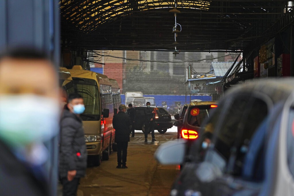 In this file photo dated Jan. 31, 2021, a convoy of vehicles carrying the WHO team enters the interior of the Huanan Seafood Market in Wuhan in centra...