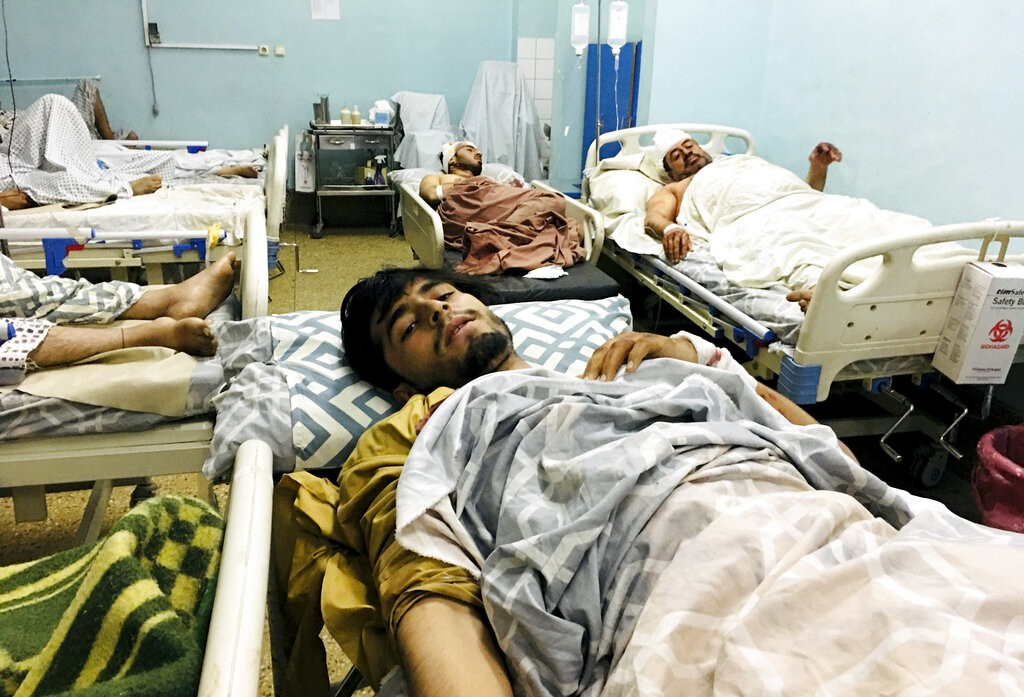 Wounded Afghans lie on a bed at a hospital after deadly explosions outside the airport in Kabul, Afghanistan, Thursday, Aug. 26, 2021.