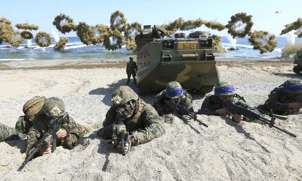 U.S. Marines (left) and South Korean Marines wearing blue headbands take part in beach landing exercise in 2016.