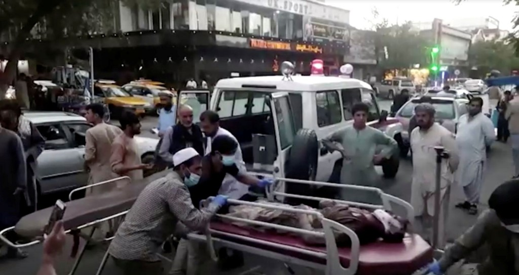 A screen grab shows people carrying an injured person to a hospital after an attack at Kabul airport, in Kabul, Afghanistan August 26, 2021. REUTERS T...