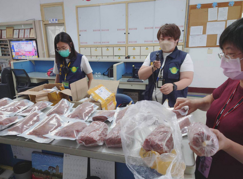 Authorities inspect the infected meat. (Photo provided by officials in Kaohsiung's Gangshan Precinct)