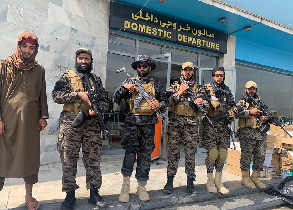 Taliban fighters stand guard inside the Hamid Karzai International Airport after the U.S. withdrawal in Kabul, Afghanistan, Tuesday, Aug. 31, 2021. Th...