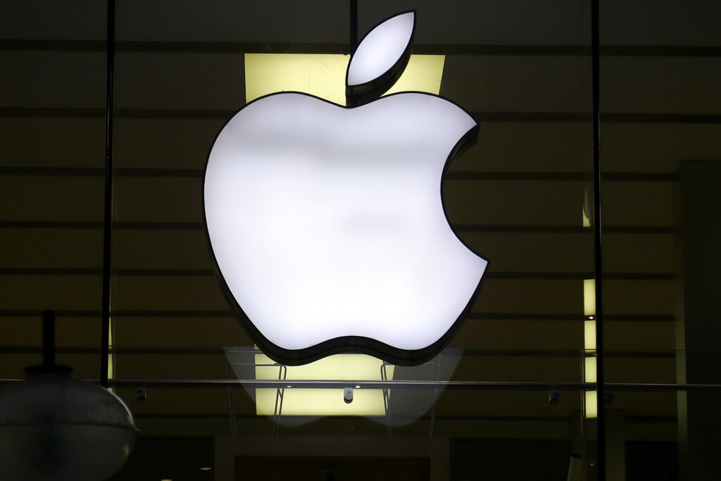 In this Wednesday, Dec. 16, 2020 file photo, the logo of Apple is illuminated at a store in the city center in Munich, Germany.