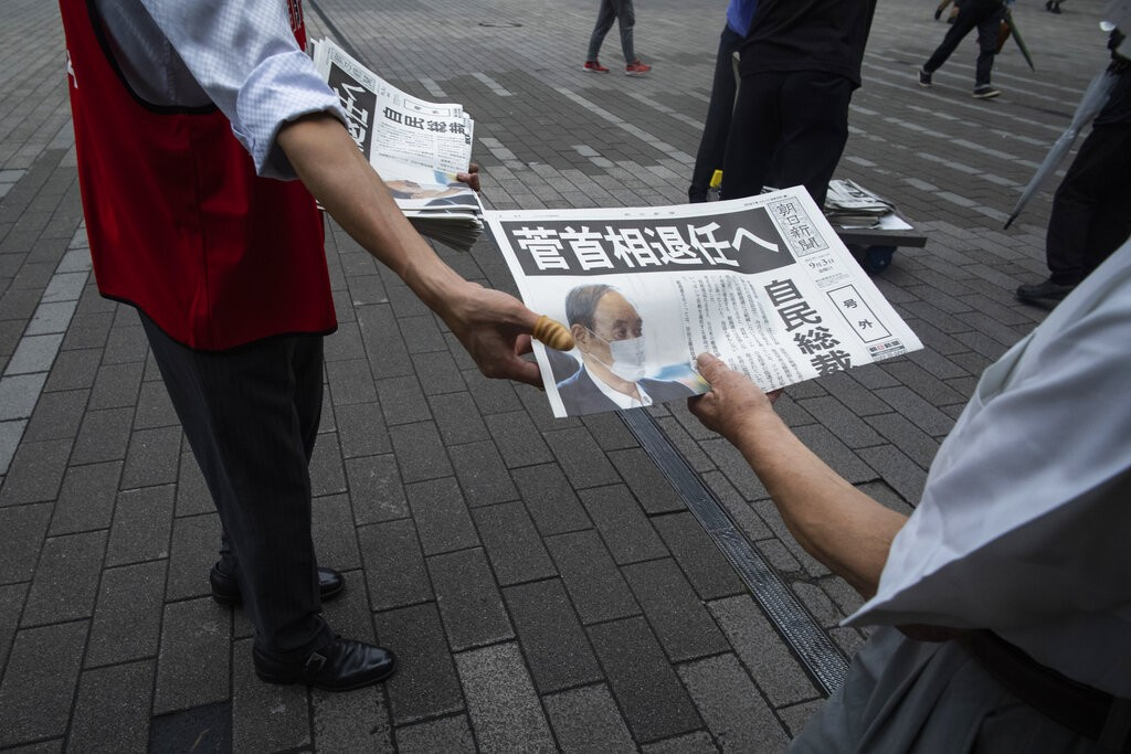 A staffer for a Japanese newspaper hands out a copy of the extra issue for Japanese Prime Minister Yoshihide Suga's announcement of not running fo...