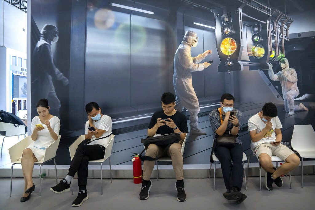 Visitors use their smartphones as they sit in front of a mural at the China International Fair for Trade in Services (CIFTIS) in Beijing, Friday, Sept...