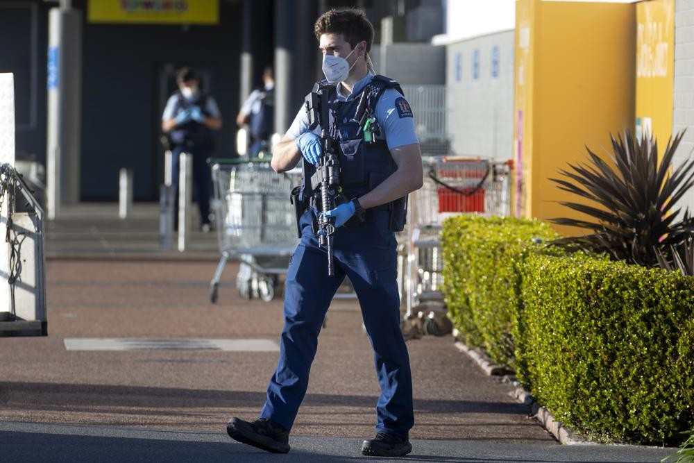 Armed New Zealand police standing outside a supermarket where an extremist stabbed shoppers.
