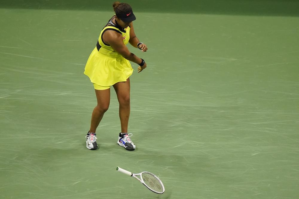 Naomi Osaka throws down her racket during a match.