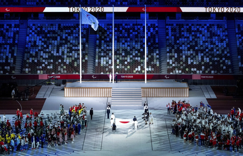 The national flag of Japan is handed over to members of the Japan Self-Defense Forces during the closing ceremony of the Tokyo 2020 Paralympic Games i...