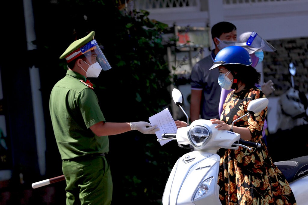 A policeman hands back the travel permit to a commuter after checking at a street checkpoint in Vung Tau, Vietnam on Monday, Sept. 6, 2021.