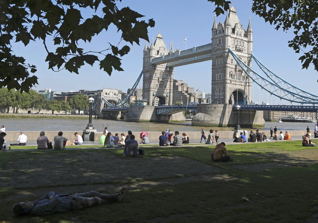 A man sleeps in the shade under a tree on the grass near Potters Field overlooking Tower Bridge in London, Sept. 7, 2021 as temperatures were getting ...