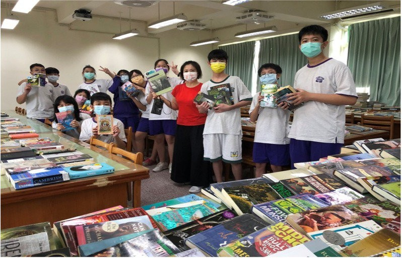 Students at Taipei Municipal Dong-Hu Junior High School and their donated books. (UDN photo)