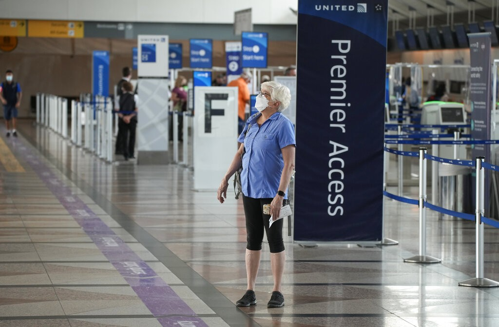 A lone traveler wears a face covering as she stops to check the departure monitors across from the United Airlines ticketing counter in the main termi...