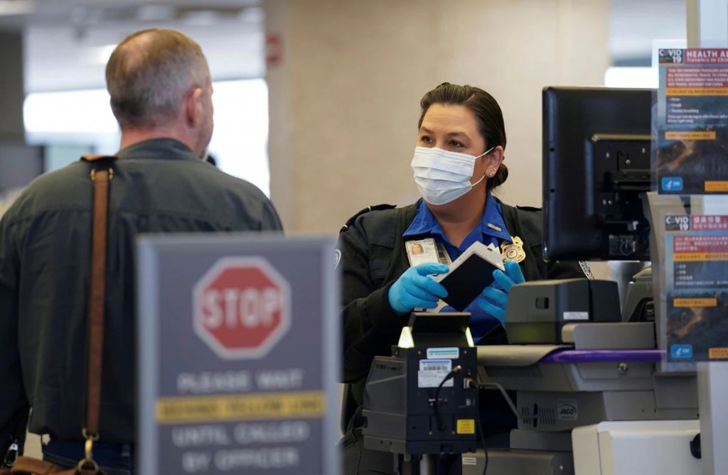 A TSA officer wearing a face mask clears a departing passenger at Dulles International Airport in Dulles. REUTERS/Kevin Lamarque
