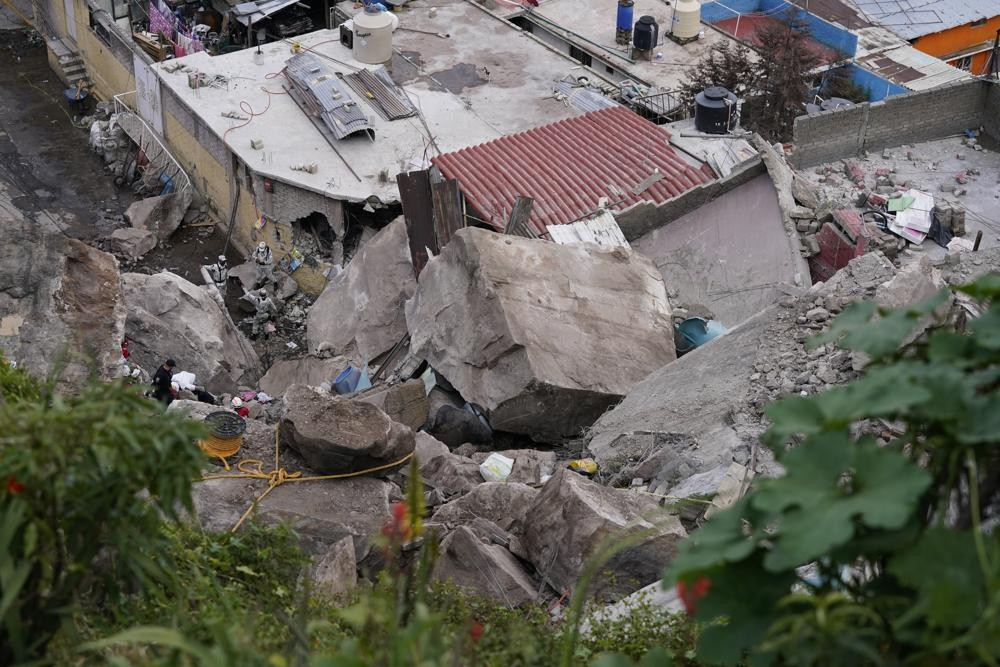 Boulders that plunged from a mountainside rests among homes in Tlalnepantla, on the outskirts of Mexico City, when a mountain gave way on Friday, Sept...