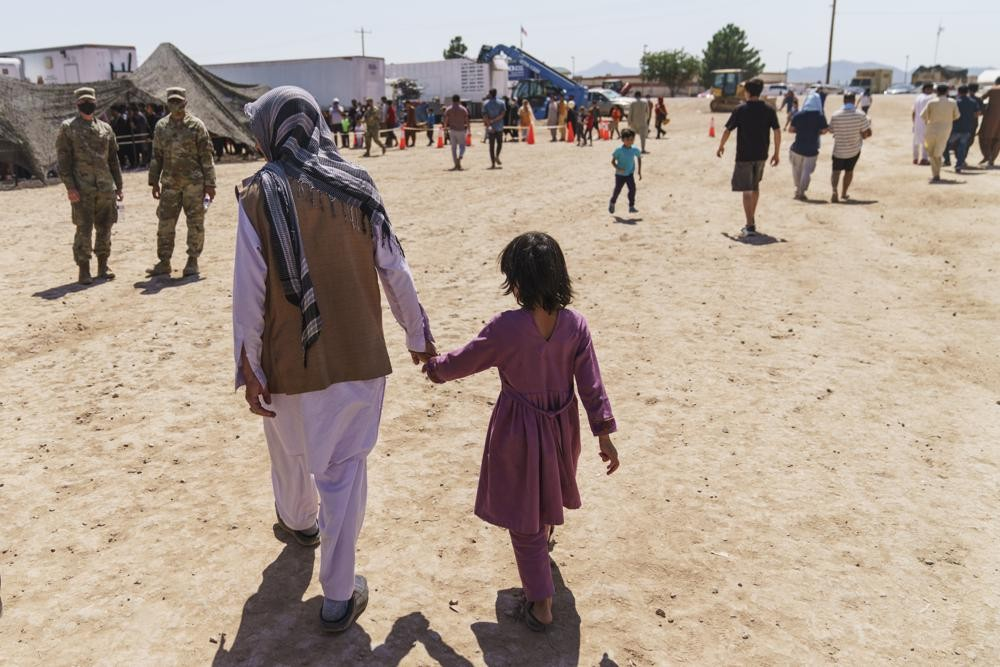 A man walks with a child through Fort Bliss' Doña Ana Village where Afghan refugees are being housed, in New Mexico, Friday, Sept. 10, 2021...