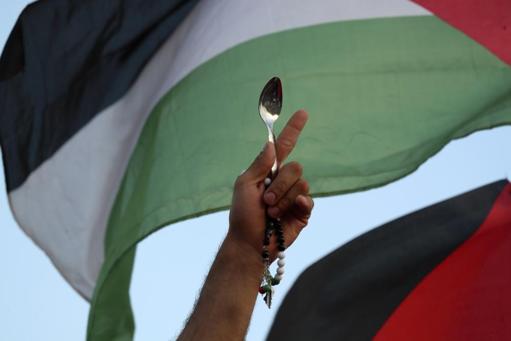 A protester holds a Palestinian flag and a spoon, which has become a symbol celebrating the six Palestinian prisoners who recently tunneled out of Gil...
