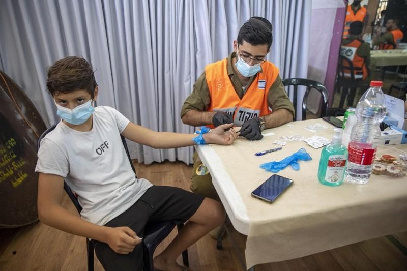 以色列男孩接受COVID-19抗體檢驗(圖/AP)
