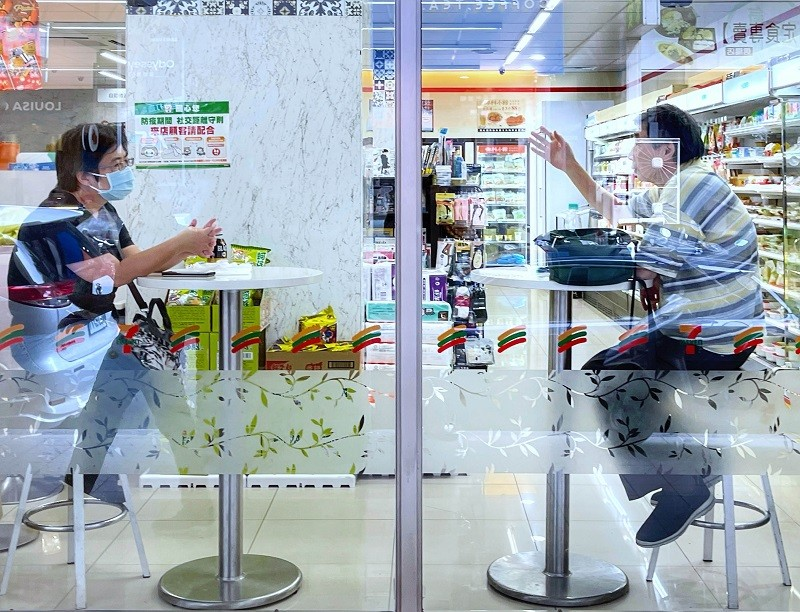 圖為13日台北市一間超商內,民眾依照防疫規定,保持社交距離,隔桌交談。中央社