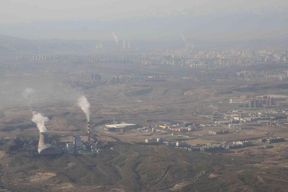 In this Wednesday, April 21, 2021 file photo, smoke and steam rise from towers at the coal-fired Urumqi Thermal Power Plant in Urumqi in western China...