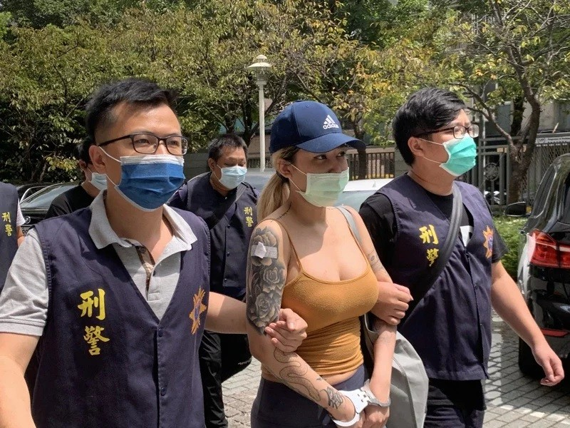 Pan (center) being escorted by CIB officers. (CIB photo)