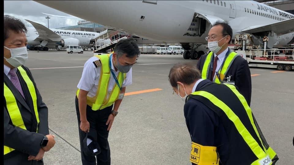 駐日代表謝長廷向載運日本捐贈的50萬劑AZ疫苗來台的機長鞠躬致意。(圖/謝長廷臉書)