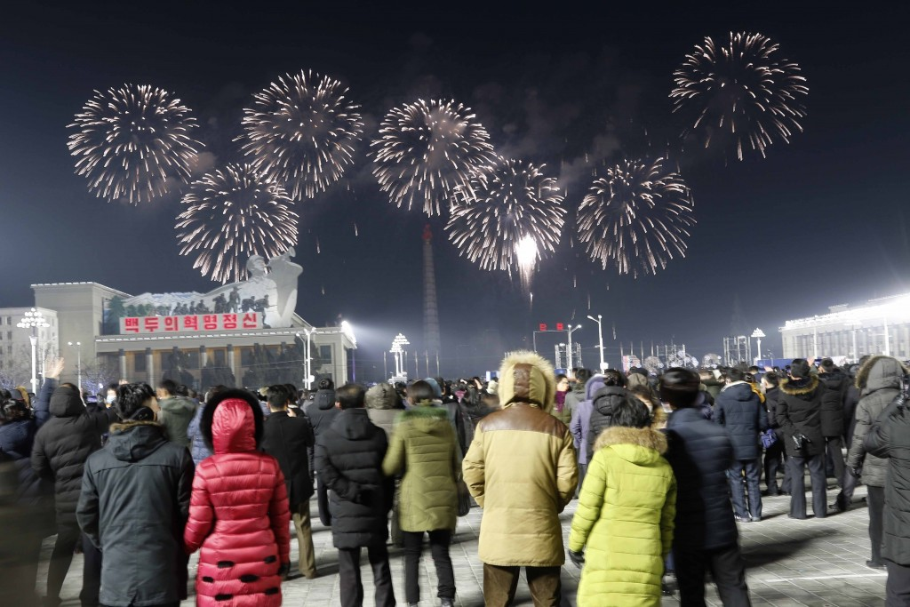 A fireworks display decorates the night sky to celebrate the New Year, as crowds of people look on, at Kim Il Sung Square in Pyongyang, North Korea, e...