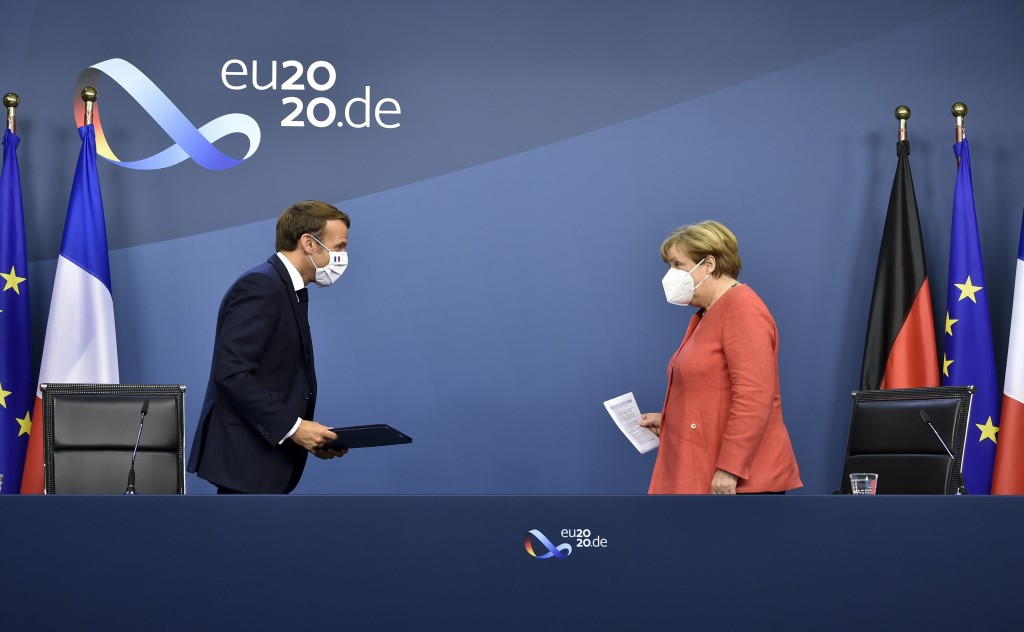 FILE - In this Tuesday, July 21, 2020 file photo, German Chancellor Angela Merkel, right, and French President Emmanuel Macron prepare to address a me...