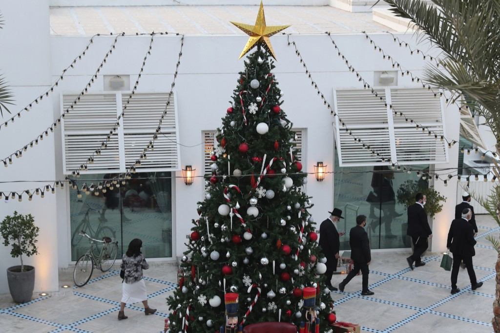 A rabbi and other guests pass a Christmas tree to take part in an Israeli wedding ceremoney in Dubai, United Arab Emirates, Thursday, Dec. 17, 2020.  ...