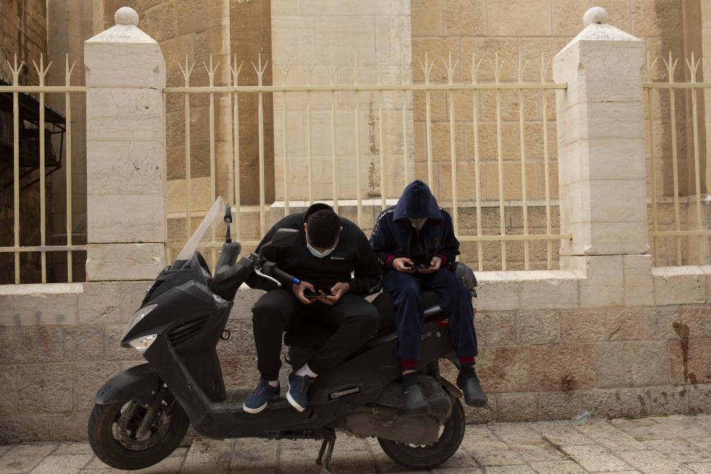 Young men scroll on their smart phones in the Old City of Jerusalem, Wednesday, Dec. 23, 2020. In the early days of the pandemic, a panicked Israel be...