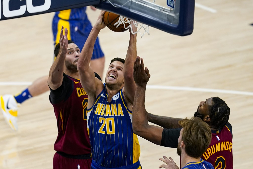 Indiana Pacers forward Doug McDermott (20) shoots between Cleveland Cavaliers forwards Larry Nance Jr. (22) and Andre Drummond during the first half o...