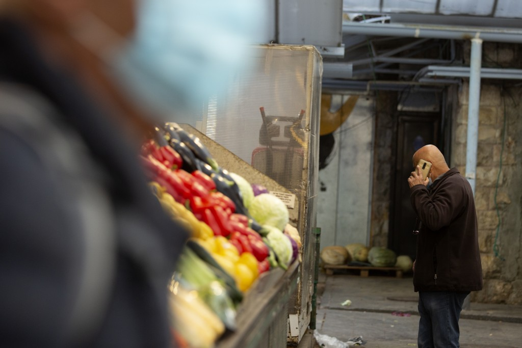 A man in a protective mask passes another man talking on his mobile phone at the Mahane Yehuda market in Jerusalem, Wednesday, Dec. 23, 2020. In the e...