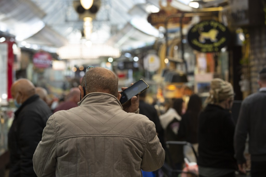 A man speaks on his mobile phone in the Mahane Yehuda market in Jerusalem, Wednesday, Dec. 23, 2020. In the early days of the pandemic, a panicked Isr...