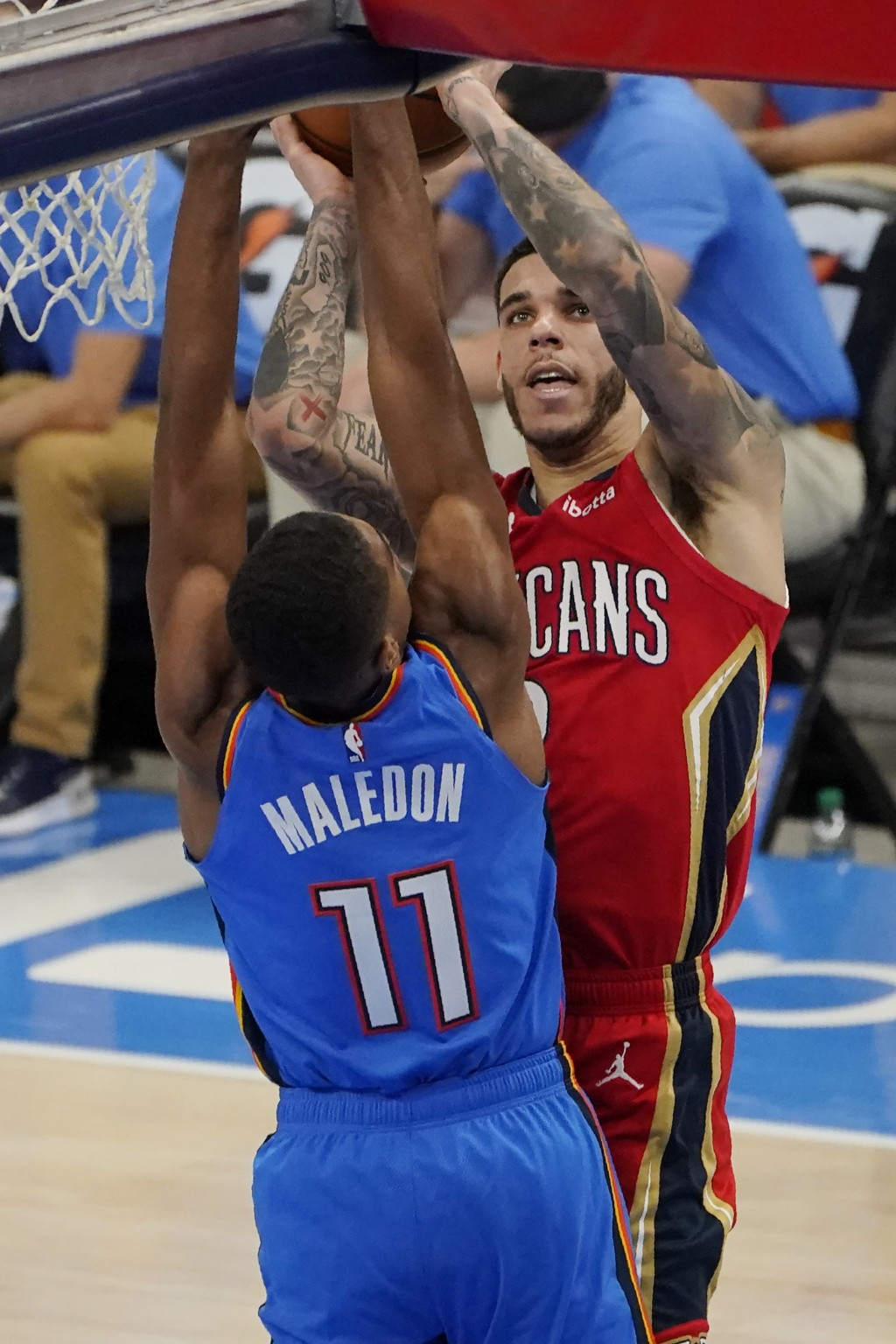 New Orleans Pelicans guard Lonzo Ball, right, shoots over Oklahoma City Thunder guard Theo Maledon (11) in the second half of an NBA basketball game T...