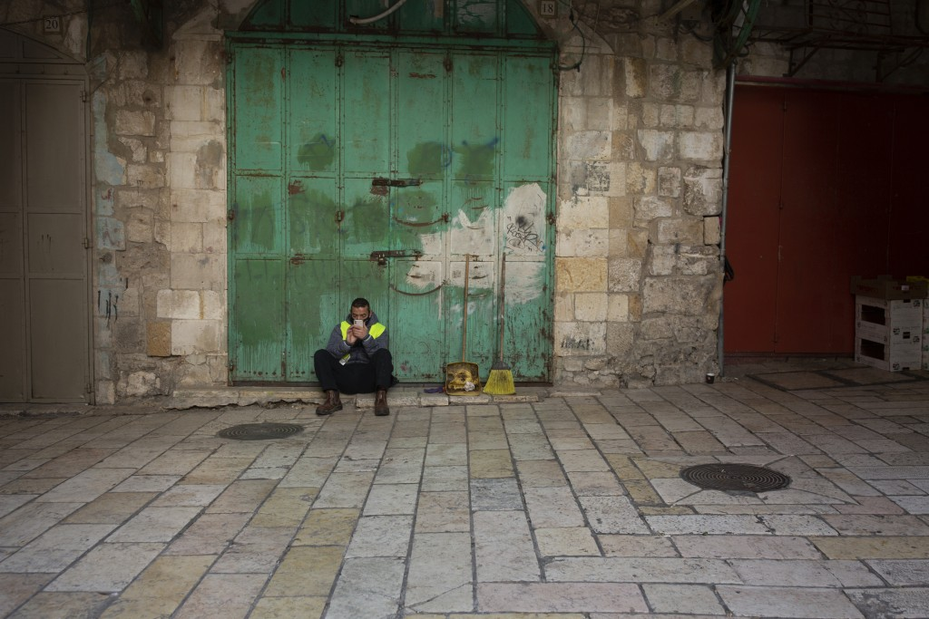 A municipal worker uses his mobile phone in the Old City of Jerusalem, Monday, Dec. 28, 2020 during a third lockdown to curb the spread of the coronav...