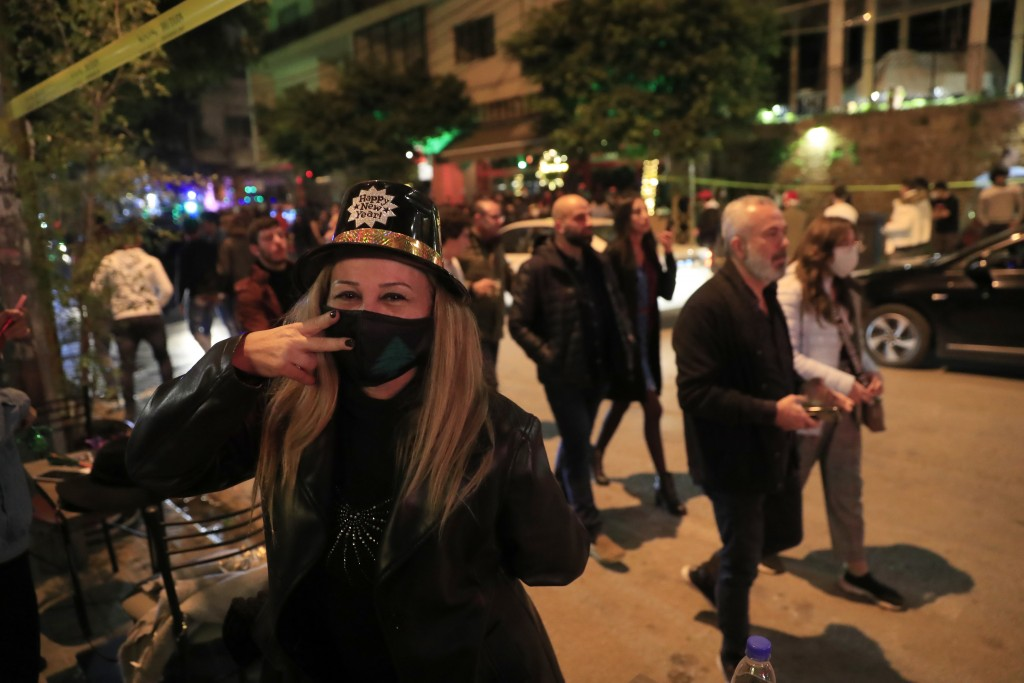 A Lebanese woman wears a protective mask to prevent the spread of coronavirus, as she celebrates the New Year outside a pub, in Beirut, Lebanon, early...