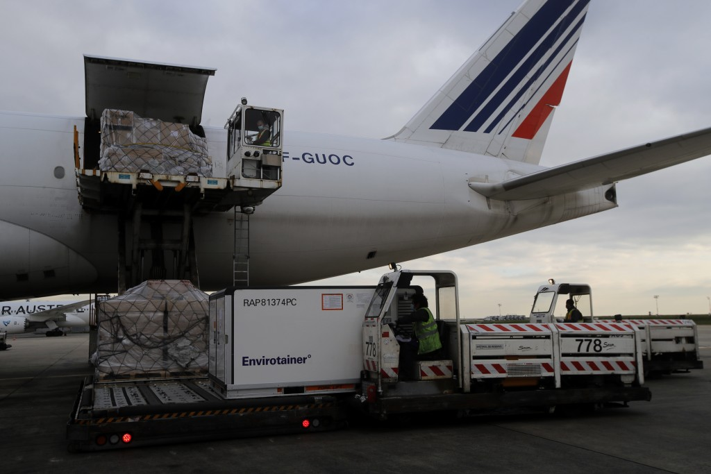 FILE - In this Wednesday, Nov. 25, 2020 file photo, Air France cargo workers load equipment and pharmaceutical containers onto a cargo plane at Roissy...