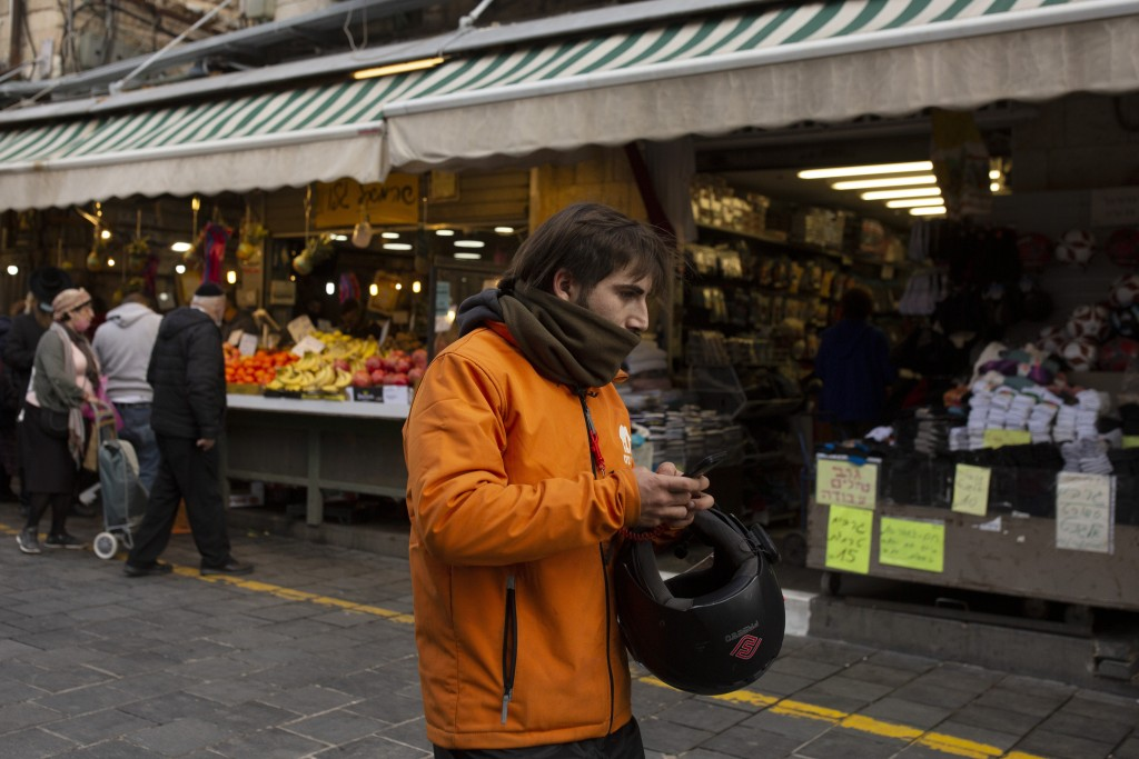 A dood delivery driver carries his smart phone in the Mahane Yehuda market in Jerusalem, Wednesday, Dec. 23, 2020. In the early days of the pandemic, ...