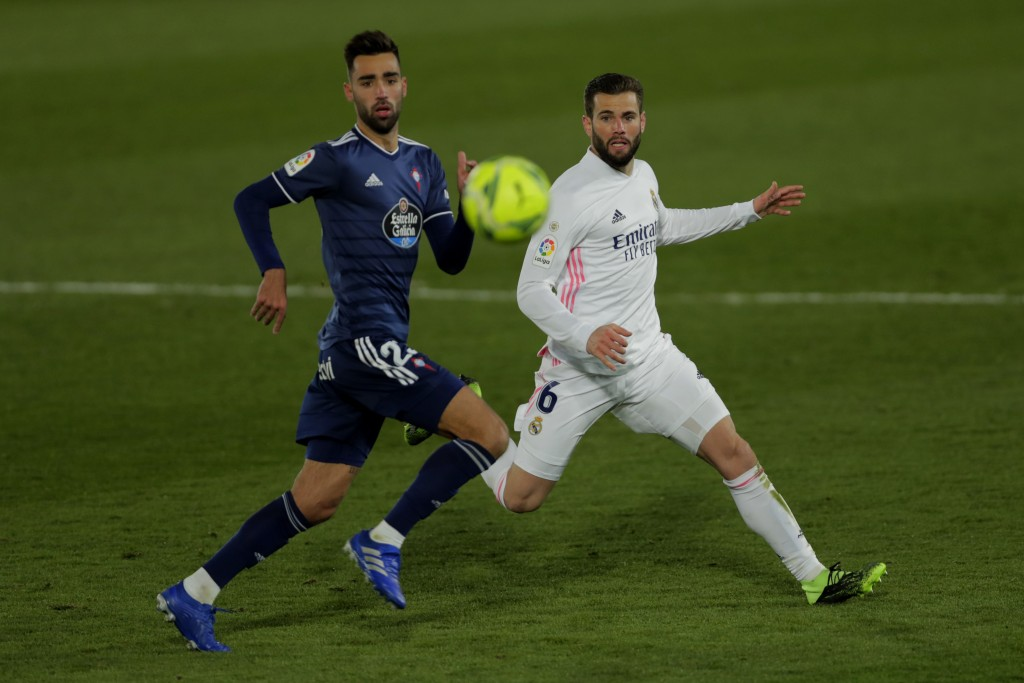 Real Madrid's Nacho, right, runs for the ball with Celta Vigo's Brais Mendez during the Spanish La Liga soccer match between Real Madrid and Celta Vig...