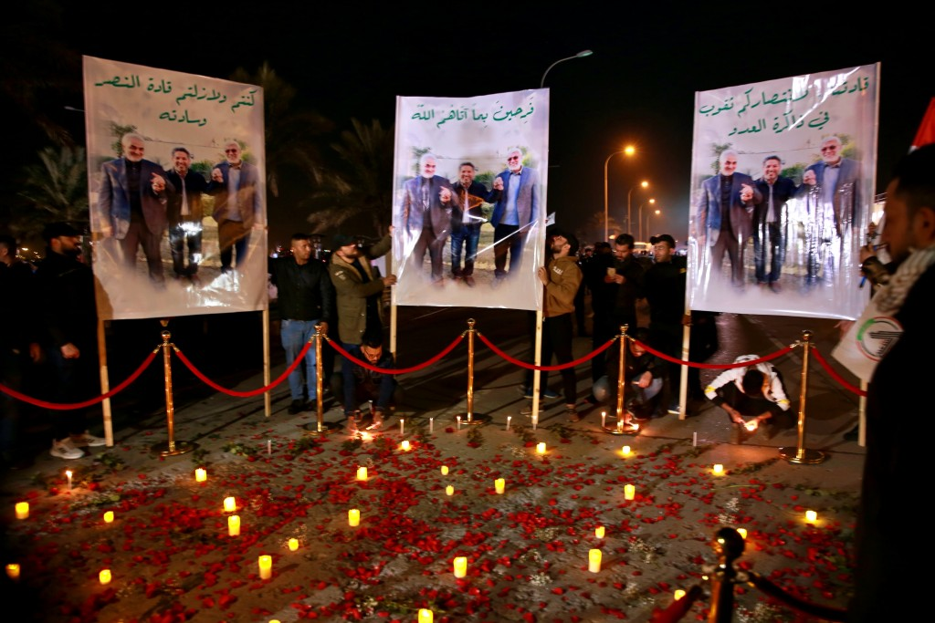 Popular Mobilization Forces and their supporters light candles at Baghdad's international airport on Saturday, Jan. 2, 2021, on the anniversary of the...