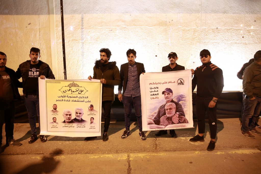 Popular Mobilization Forces and their supporters hold posters of Abu Mahdi al-Muhandis, deputy commander of the PMF and Gen. Qassem Soleimani, head of...