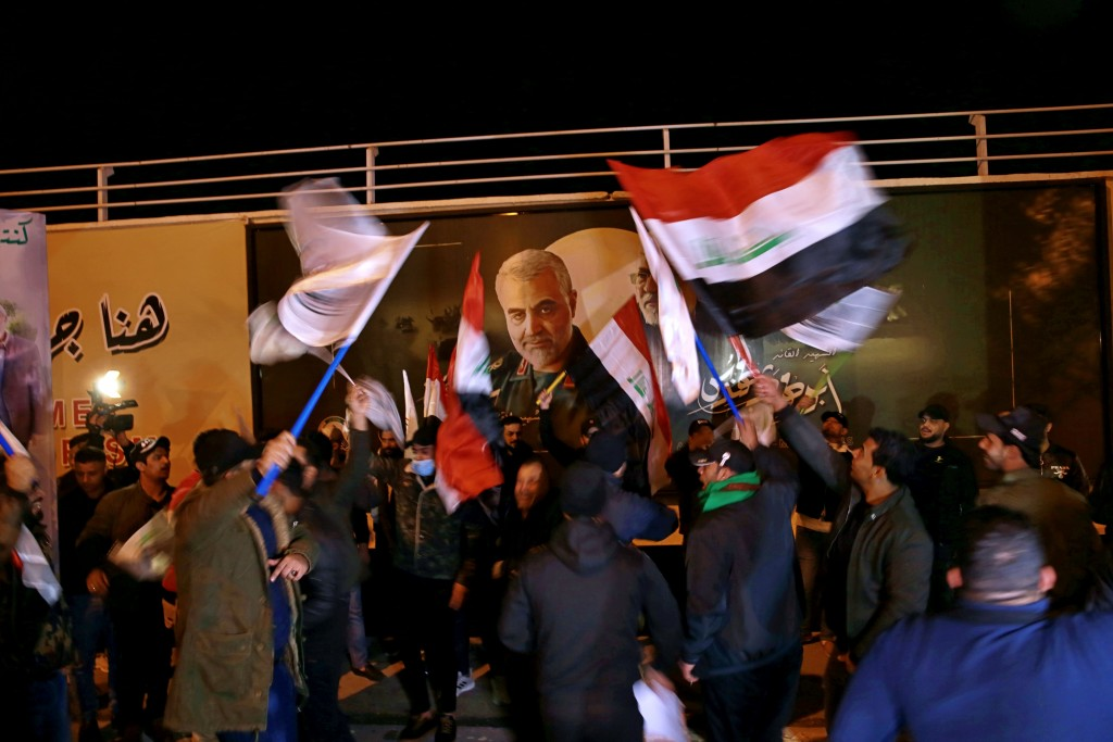 Popular Mobilization Forces and their supporters chant slogans against the United States at Baghdad's international airport on Saturday, Jan. 2, 2021,...