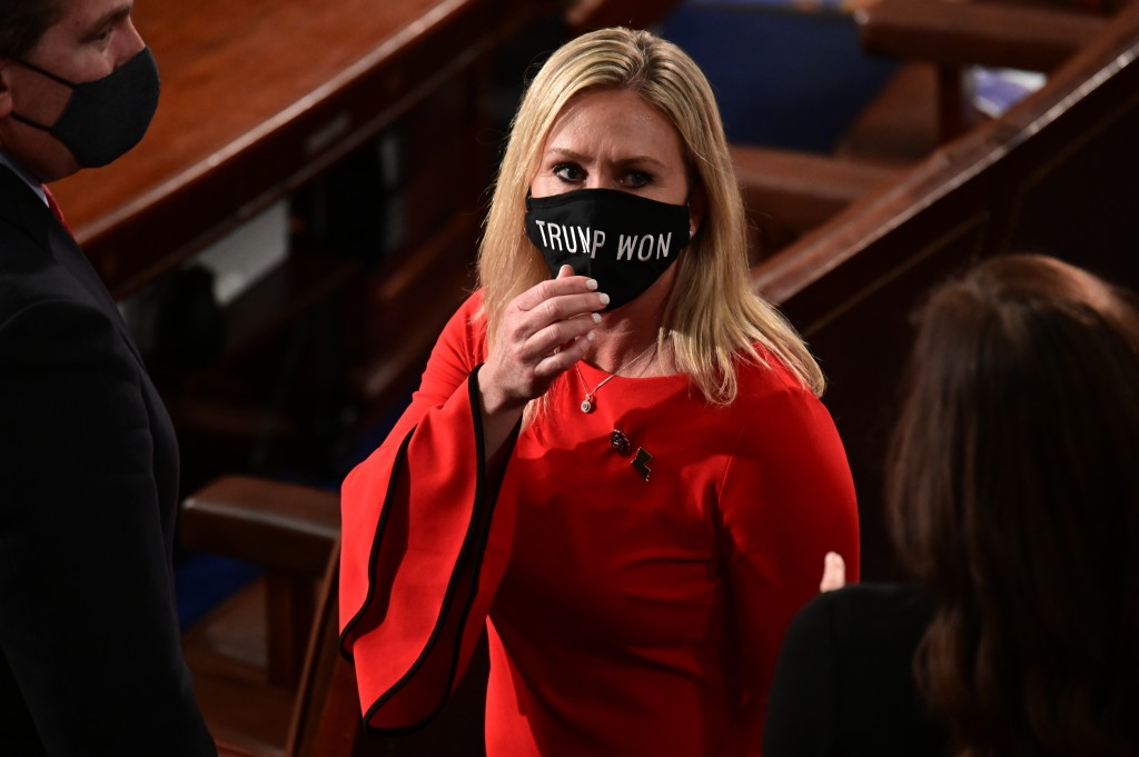 """Rep. Marjorie Taylor Greene, R-Ga., wears a """"Trump Won"""" face mask as she arrives on the floor of the House to take her oath of office on opening day o..."""