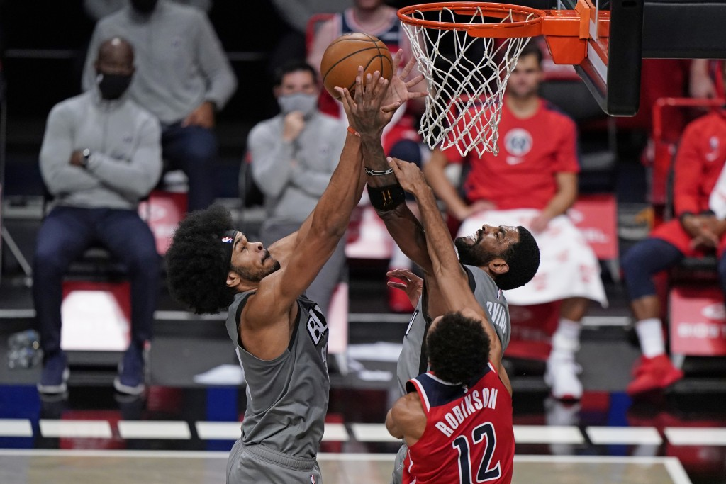 Brooklyn Nets center Jarrett Allen, left, and guard Kyrie Irving, center, battle for a rebound in front of Washington Wizards guard Jerome Robinson, r...
