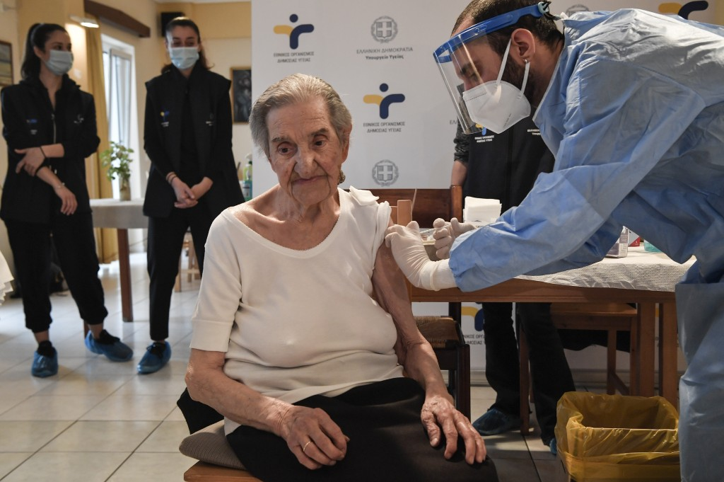 An elderly woman gets a vaccination at a nursing house in Athens, Monday, Jan. 4, 2021. Vaccinations were expanded from 9 to 50 hospitals nationwide o...