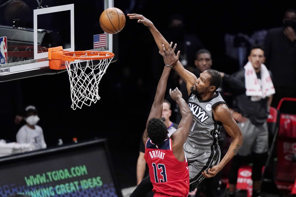 Brooklyn Nets forward Kevin Durant, right, dunks over Washington Wizards center Thomas Bryant, left, during the second quarter of an NBA basketball ga...