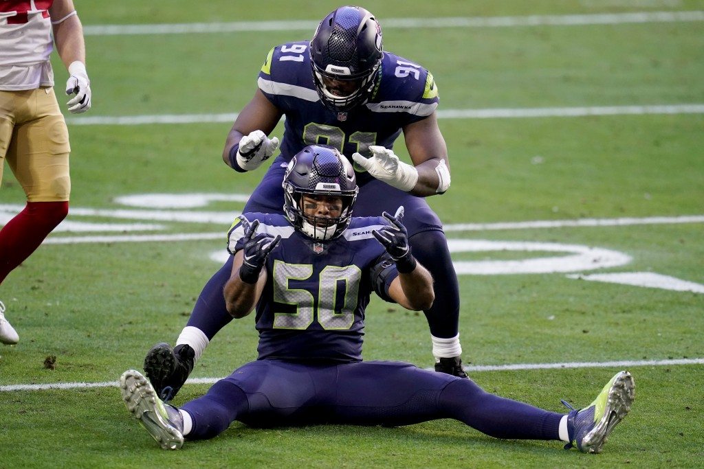 Seattle Seahawks outside linebacker K.J. Wright (50) and defensive end L.J. Collier (91) celebrate a defensive stop against the San Francisco 49ers du...