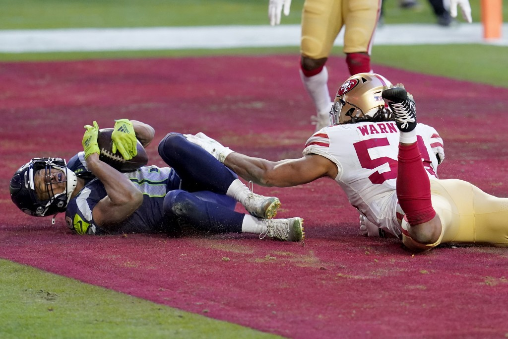 Seattle Seahawks wide receiver Tyler Lockett scores a touchdown as San Francisco 49ers middle linebacker Fred Warner (54) defends during the second ha...