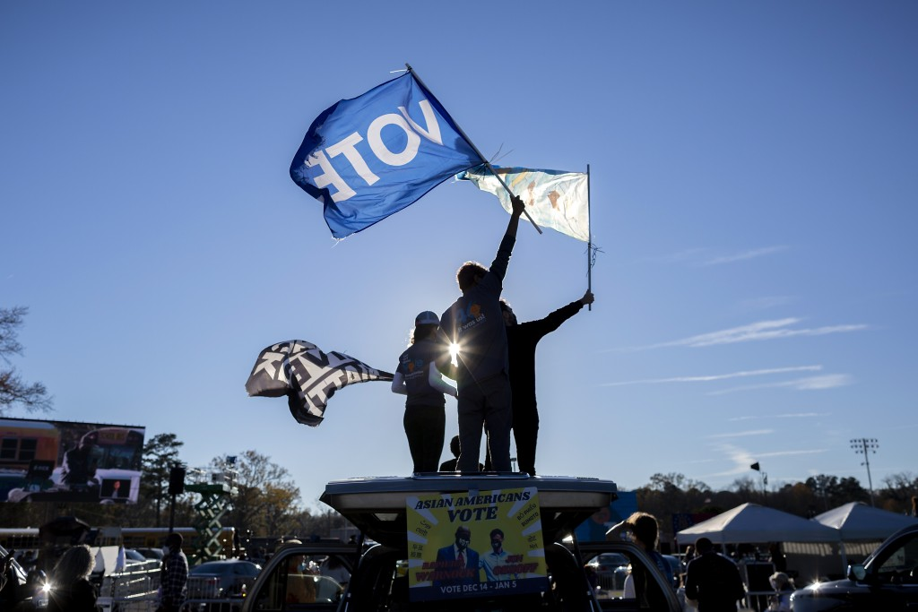Supporters wave flags while they wait for Vice President-elect Kamala Harris at a drive-in rally in Savannah, Ga., Sunday, Jan. 3, 2021, in Savannah, ...