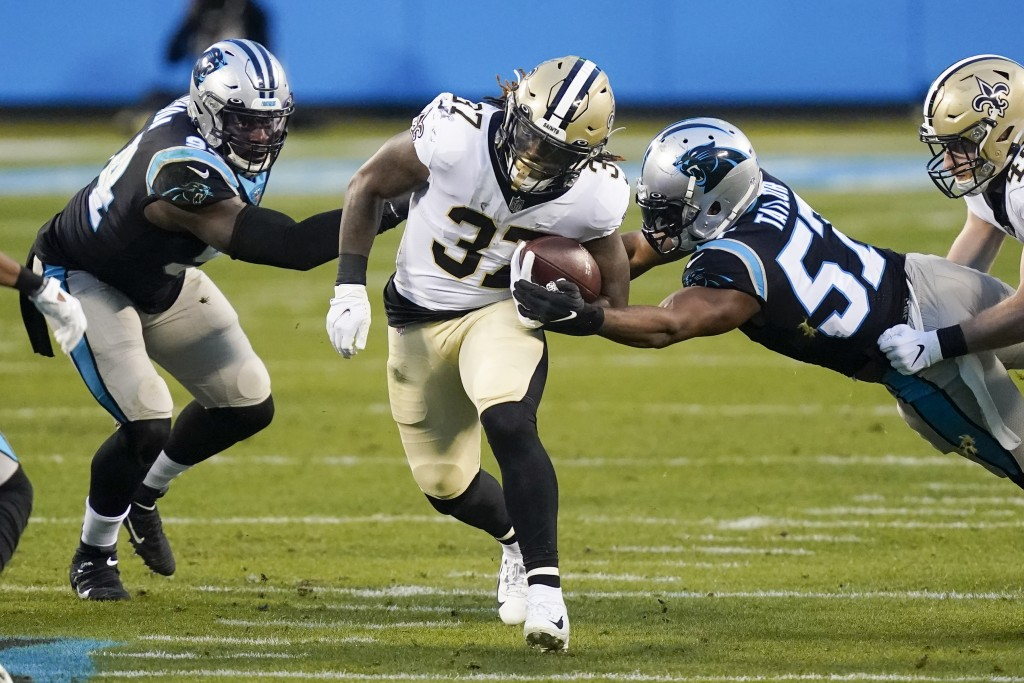 New Orleans Saints running back Tony Jones runs between Carolina Panthers defensive end Efe Obada, left, and outside linebacker Adarius Taylor during ...