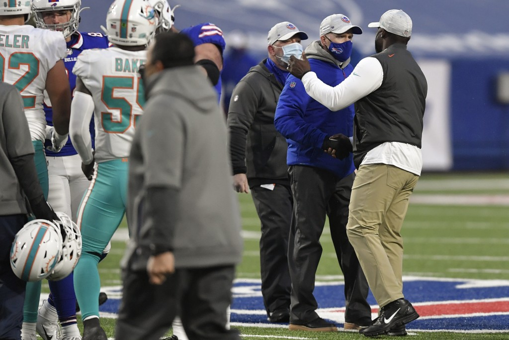 Buffalo Bills head coach Sean McDermott, second from right, meets with Miami Dolphins head coach Brian Flores, right, on the field after an NFL footba...